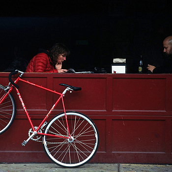 Couple at cafe with red bicycle | NIKON 105MM F2.5